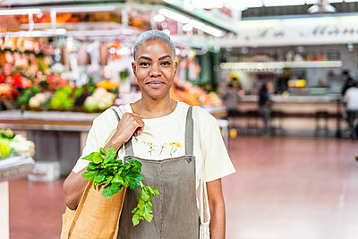 Portrait of smiling woman buying groceries in a market hall - p300m2179899 by VITTA GALLERY