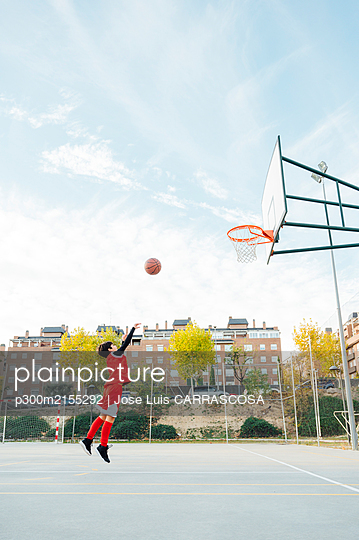 Boy playing basketball on outdoor court - p300m2155292 by Jose Luis CARRASCOSA