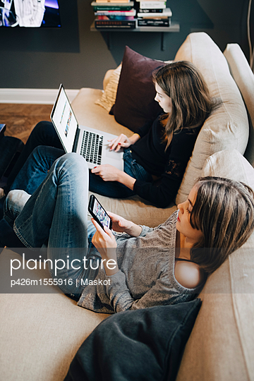 Smiling girls using laptop and mobile phone while resting on sofa at home - p426m1555916 by Maskot