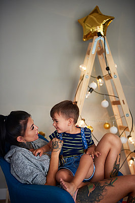 Happy boy with his mother at home at Christmas time - p300m2041550 by gpointstudio