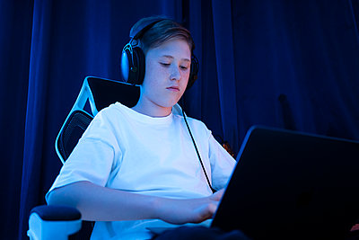 Boy with headphones using laptop at home - p300m2300021 by Vasily Pindyurin