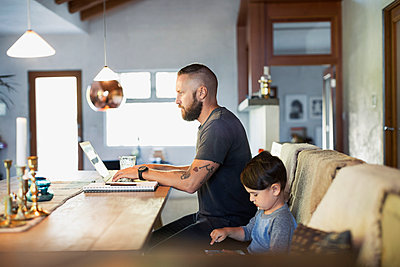 Side view of father and son using technologies at dining table - p426m1062734f by Maskot