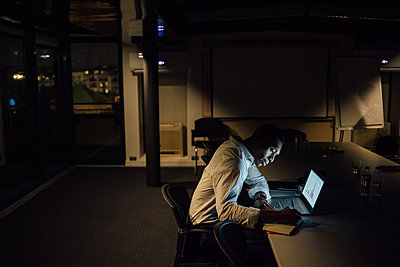 Young businessman in office at night making notes from laptop - p429m2091388 by Eugenio Marongiu