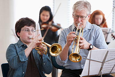 Student playing trumpet with teacher - p555m1479275 by KidStock