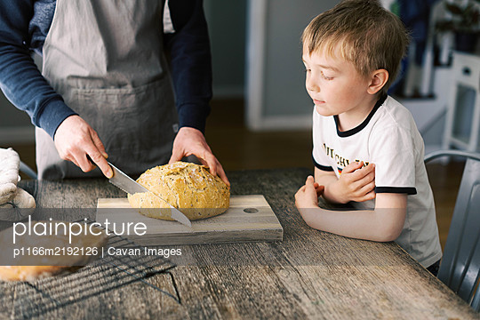 Man cutting a fresh loaf of bread for lunch. - p1166m2192126 by Cavan Images