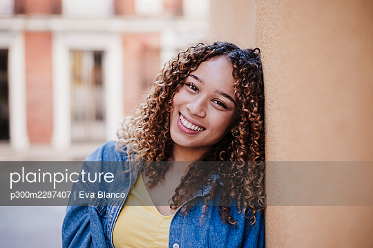 Smiling woman leaning on wall outdoors - p300m2287407 by Eva Blanco