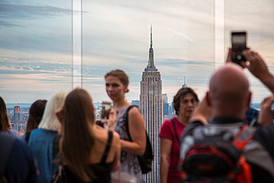 Tourists take photographs of the Empire State Building - p1057m1466850 by Stephen Shepherd