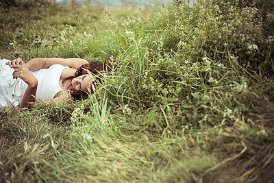 Woman lying on grassy field - p1166m1172922 by Cavan Images