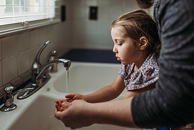 Side view of young girl having hands washed by dad - p1166m2177269 by Cavan Images