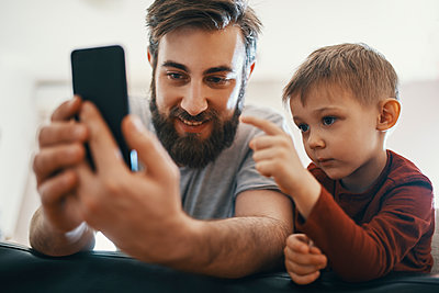 Portrait of father and little son with smartphone - p300m1581424 by Zeljko Dangubic