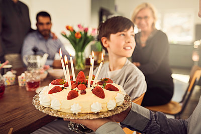 Close-up of grandfather holding birthday cake with family in background - p426m1580211 by Maskot
