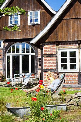 Paar mit Buch im Garten - p606m919181 von Iris Friedrich