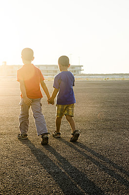 Two brothers walking together holding hands  - p794m924149 by Mohamad Itani