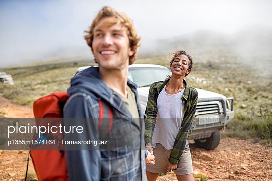 Junges Paar auf Bergtour mit SUV im Hintergrund - p1355m1574164 von Tomasrodriguez