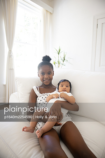 Dark-skinned girl with baby on the sofa - p1640m2254590 by Holly & John