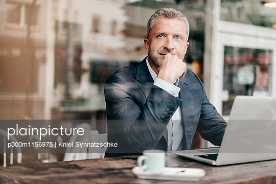 Businessman sitting in cafe, working - p300m1156975 by Kniel Synnatzschke