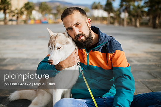 Bearded man embracing Siberian Husky while sitting on road - p300m2243172 by Miguel Frias