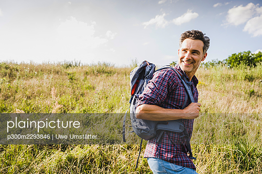 Smiling man with backpack hiking at meadow on sunny day - p300m2293846 by Uwe Umstätter
