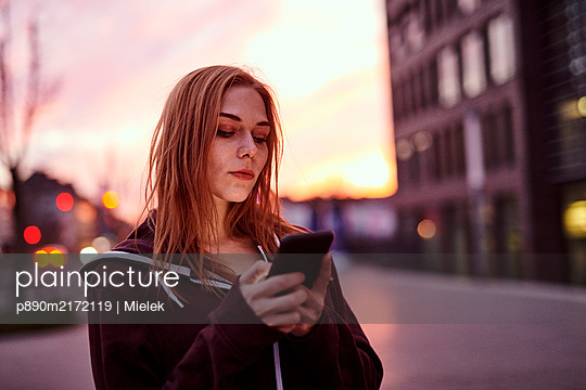 Young woman writing a text message - p890m2172119 by Mielek