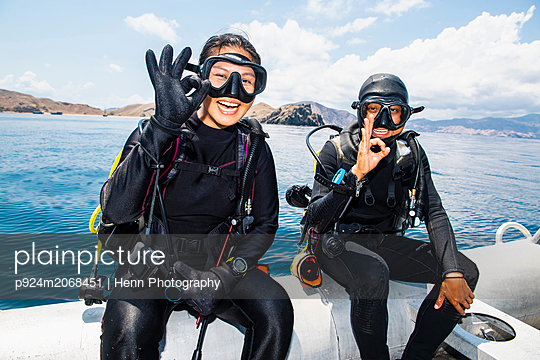 """Two scuba divers about to submerge into sea - giving the """"all ok"""" hand signal,  Komodo Island, East Nusa Tenggara, Indonesia"" - p924m2068451 by Henn Photography"