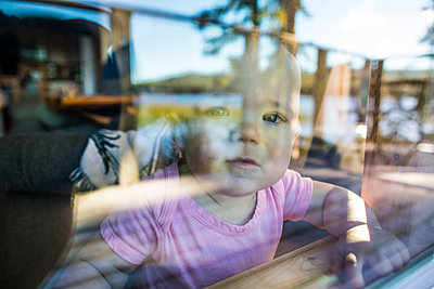 Young toddler girl looks out window with curious expectation. - p1166m2153382 by Cavan Images