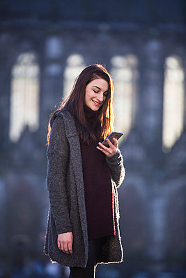 Portrait of smiling young woman looking at cell phone in autumn - p300m2029345 von Jean Schwarz