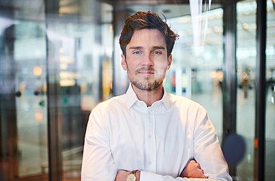 Portrait of confident young businessman behind glass pane - p300m2081393 by Philipp Nemenz