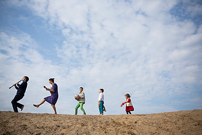 Low angle view of family enjoying on sand dune against cloudy sky - p301m1101890f by Sven Hagolani