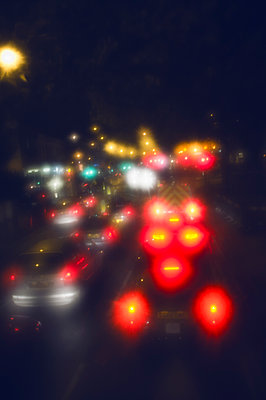 Defocused image of cars on city street at night - p301m1406539 by Michael Mann