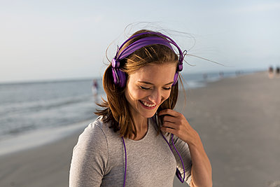 Young woman on beach with headphones - p341m1480702 by Mikesch