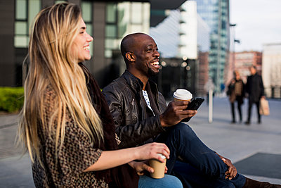 Happy young couple sitting with takeaway coffee in city - p429m1418113 by Mauro Grigollo