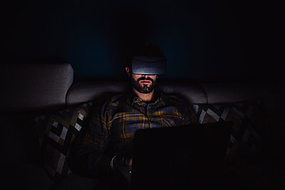 Bearded mid adult man sitting on sofa in darkness looking through virtual reality headset - p924m2097323 by Eugenio Marongiu