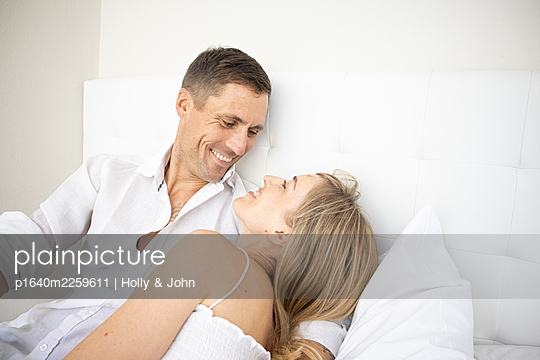 Happy couple sitting on bed, portrait - p1640m2259611 by Holly & John