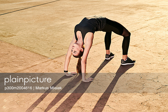 Sportive woman doing yoga, bridge position - p300m2004616 von Markus Mielek