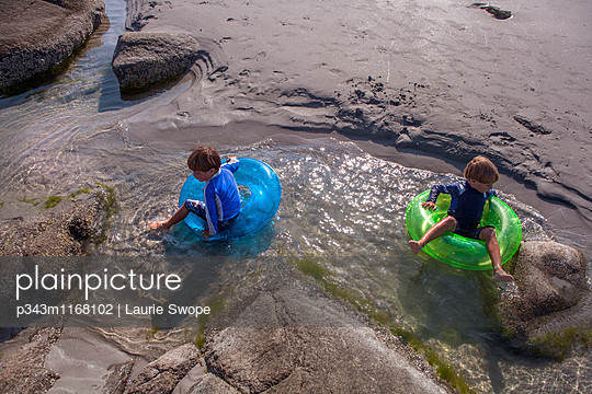 Four and Six-Year old brothers plays with inner tubes at beach. - p343m1168102 by Laurie Swope