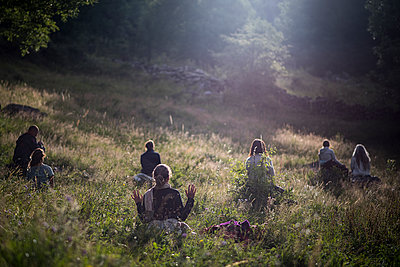 People meditating in the grass of a field at sunrise - p1007m1540353 by Tilby Vattard