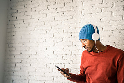 Smiling man using mobile phone while listening music through headphones against white brick wall - p300m2243340 by Rafa Cortés