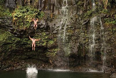 Man jumping off waterfall, Hana, Maui, Hawaii (blurred motion and digital composite). - p343m964974 by Kennan Harvey