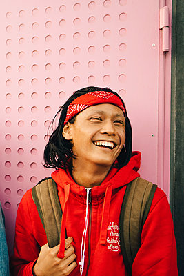 Cheerful young man looking away against wall - p426m2075168 by Maskot