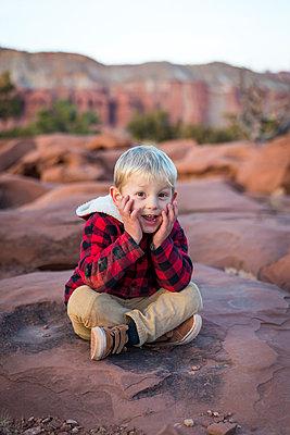Junge sitzt auf einem Felsen - p756m1584539 von Bénédicte Lassalle