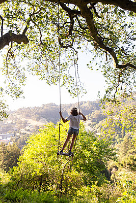 Girl on a swing, looking out on trees - p756m2211775 by Bénédicte Lassalle