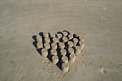 Heart-shaped sand cakes on beach - p927m1496376 by Florence Delahaye