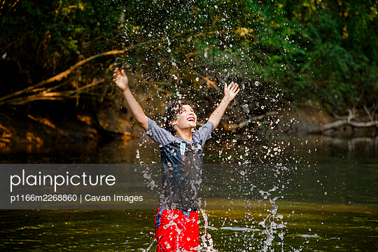 A joyful boy playing in river flings water drops high into the air - p1166m2268860 by Cavan Images