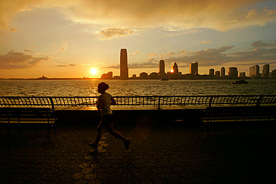 Woman running at sunset in Manhattan with Jersey City in the distance, NYC - p1028m2176261 von Jean Marmeisse