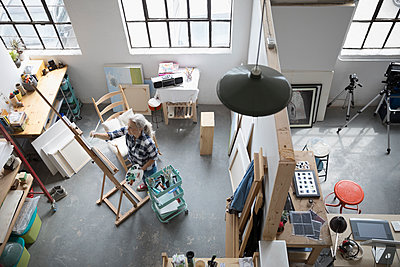 View from above female painter painting at canvas on easel in coworking space art studio - p1192m1490265 by Hero Images