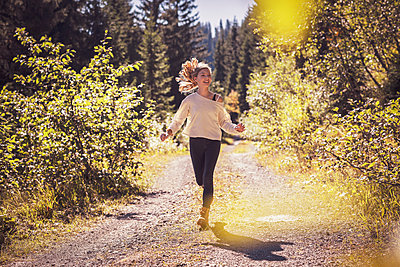 Girl running and jumping on a forest path, having fun - p300m2166720 by Studio 27