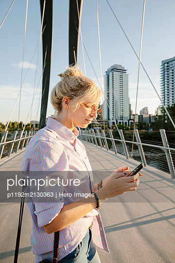 Young woman using smart phone on sunny, urban bridge - p1192m2130363 by Hero Images