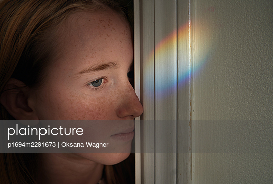 Contemplative blonde girl with freckles leaning against the wall with rainbow light beam - p1694m2291673 by Oksana Wagner