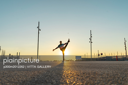 Acrobat doing movement training in city at sunrise - p300m2012262 von VITTA GALLERY