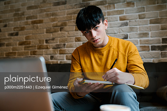 Man with laptop and book staring while sitting at cafe - p300m2251443 by Ezequiel Giménez
